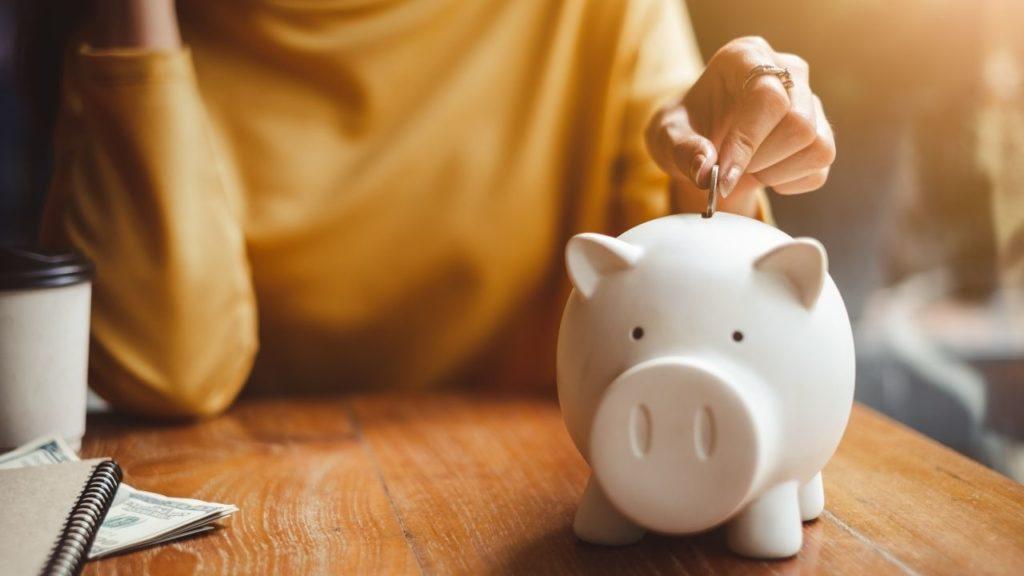 piggy bank, add money, save money, girl adds coin to piggy bank